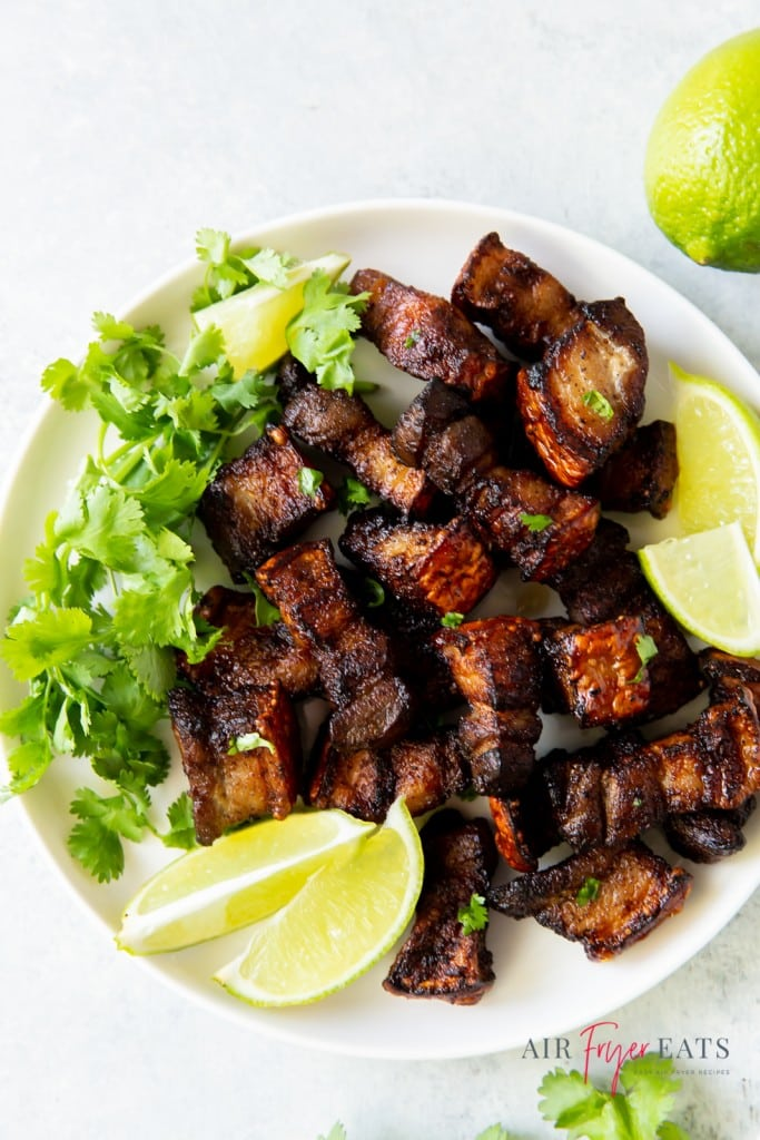 a white plate of pork belly pieces, cilantro, and lemon wedges
