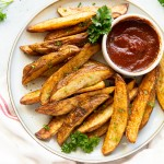 a plate of seasoned, cooked potato wedges with a side cup of ketchup.