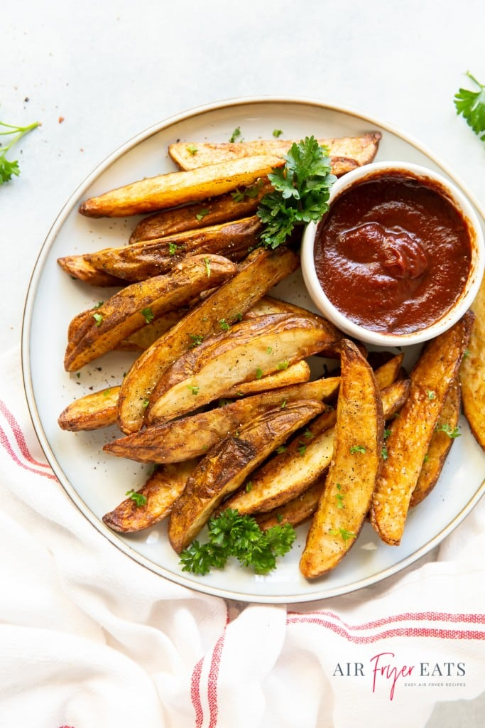 a plate of seasoned, cooked potato wedges with a side cup of barbecue sauce, garnished with curley parsley.