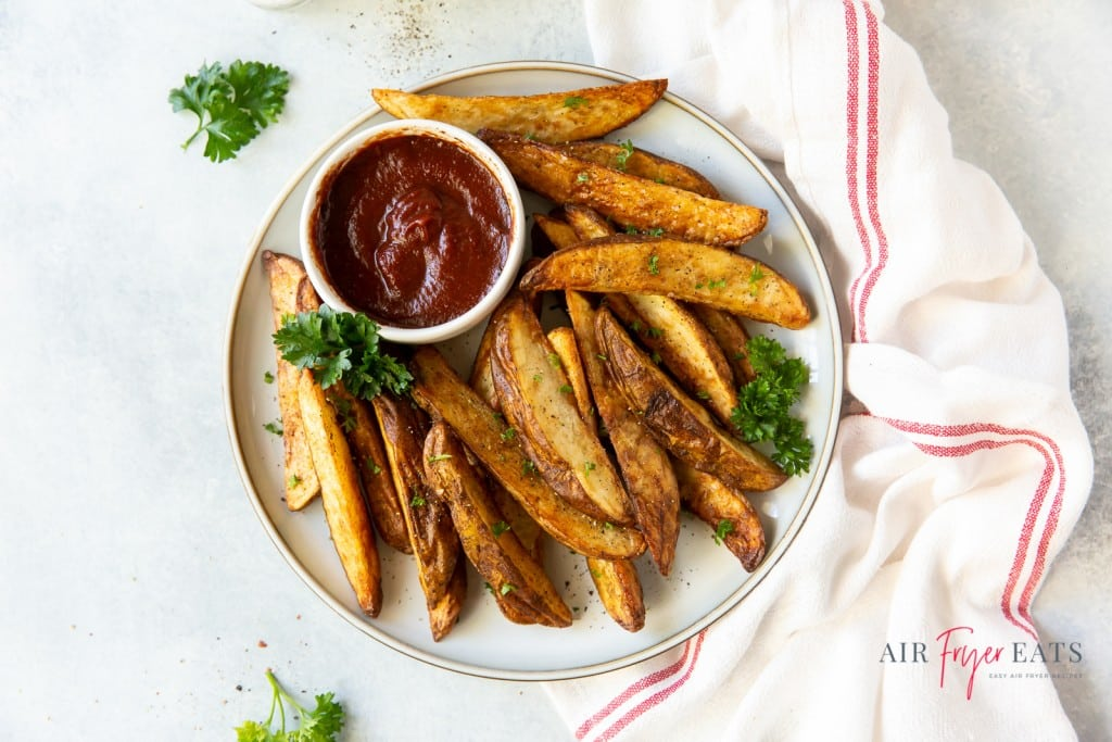 a white plate of potato wedges with a side of barbecue sauce, on a counter next to a white and red striped towel.