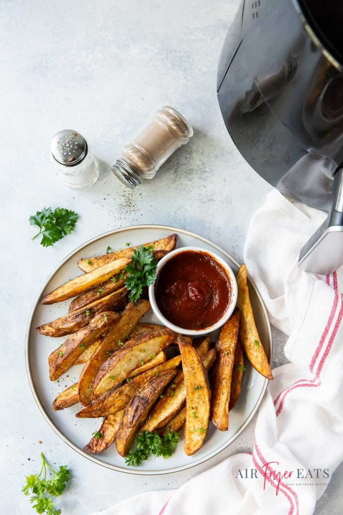 a white plate of potato wedges and ketcup, next o an air fryer basket and salt and pepper shakers