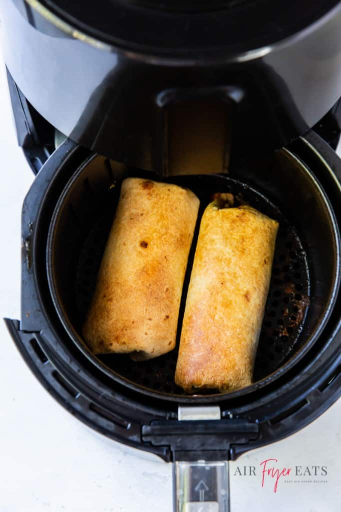 a round air fryer basket with two chimichangas inside.