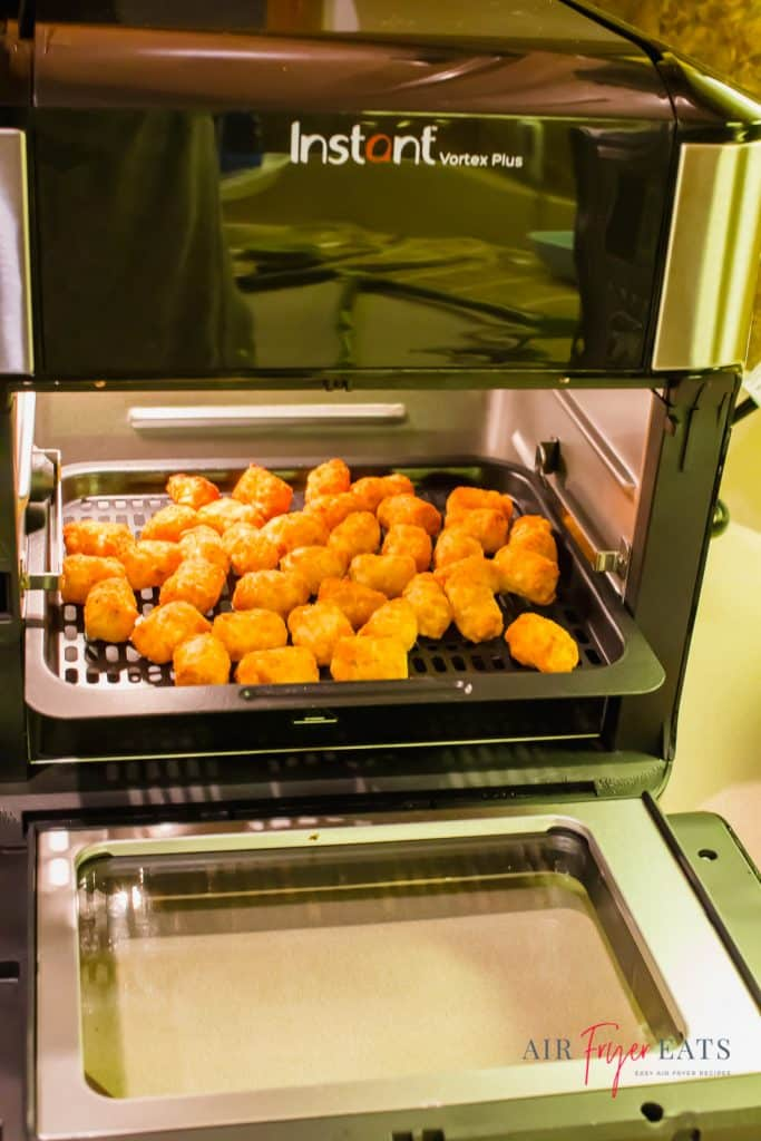 picture of instant vortex plus air fryer oven with door open and tater tots inside