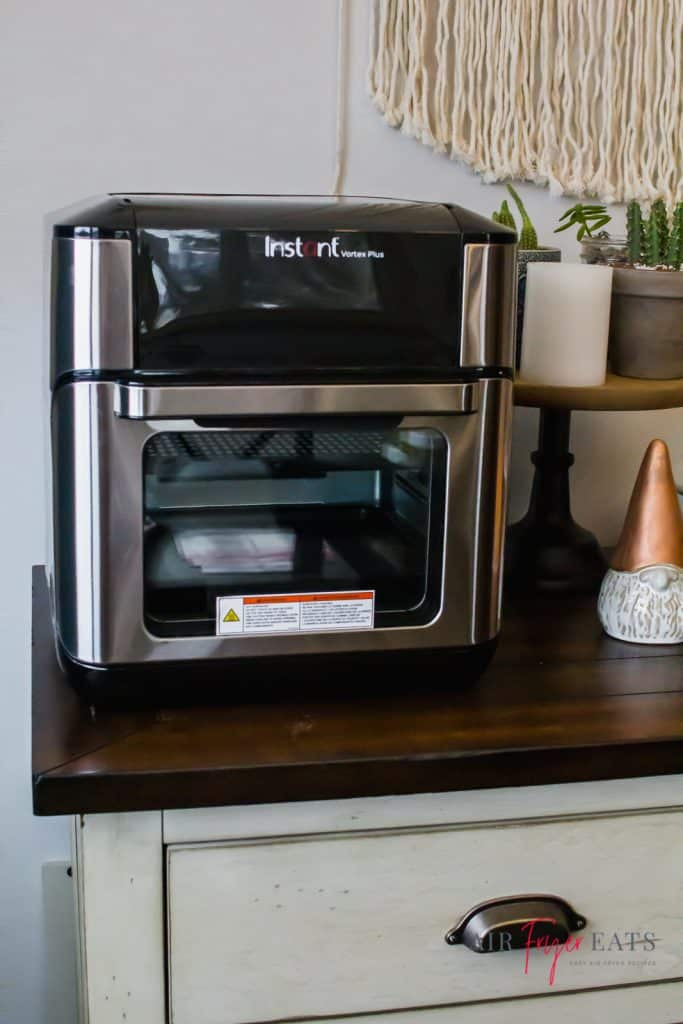 instant vortex plus air fryer oven sitting on a white buffet cabinet with a white nome with a cooper hat to the right and green catus to the top right.