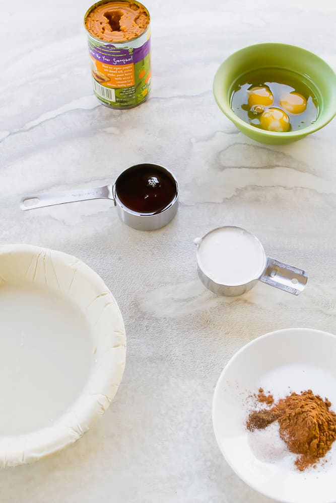 Ingredients for making pumpkin pie on a marble counter. There is a bowl of cracked eggs, a cup of maple syrup, a cup of cocunut milk, spices, a can of pumpkin and a pre-made pie shell.