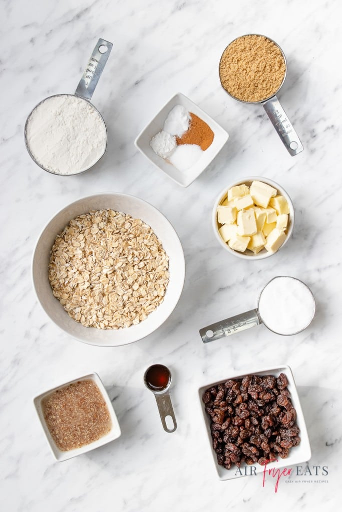 Ingredients for air fryer oatmeal cookies, each in separate bowls on a marble countertop.
