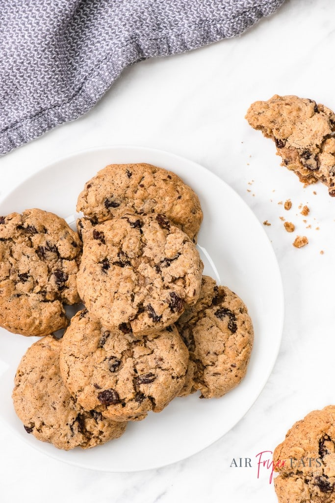 a plate of oatmeal raisin cookies next to a blue kitchen towel.
