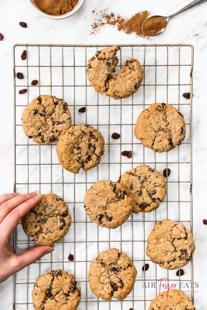 A cooling rack filled with oatmeal raisin cookies with a hand grabbing one.