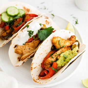 Three soft shelled tacos in a holder on top of a plate. Tacos filled with chicken fajita mix and guacamole, herbs, and cucumbers.