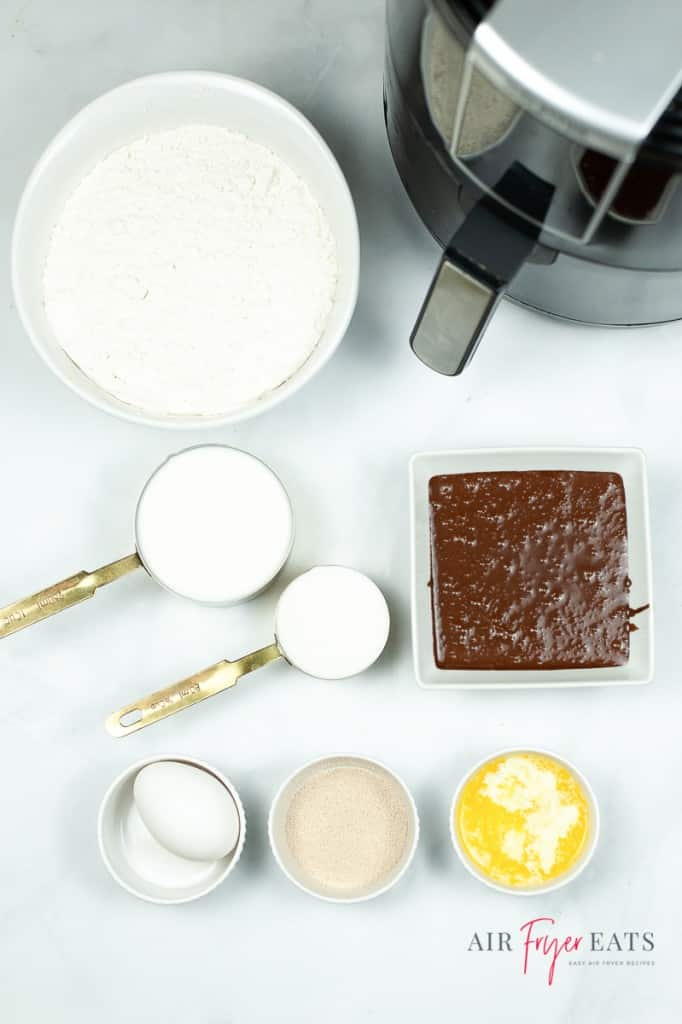 Ingredients for chocolate glazed donuts all in separate bowls next to an air fryer