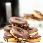a white plate toped with a stack of 6 donuts that are iced with chocolate