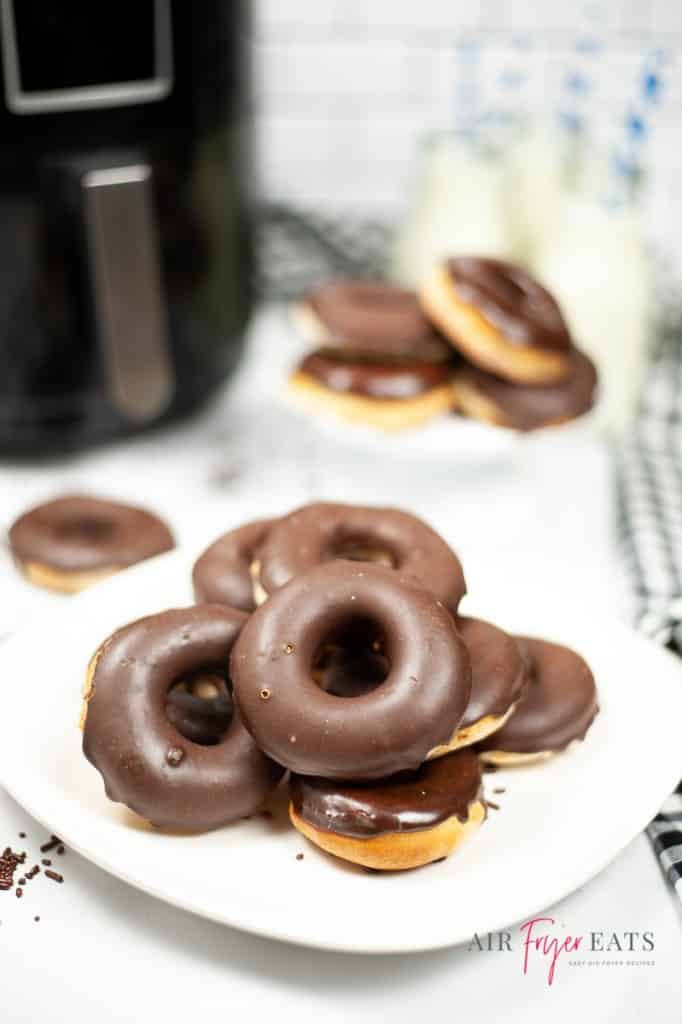 a white plate filled with glazed chocolate donuts