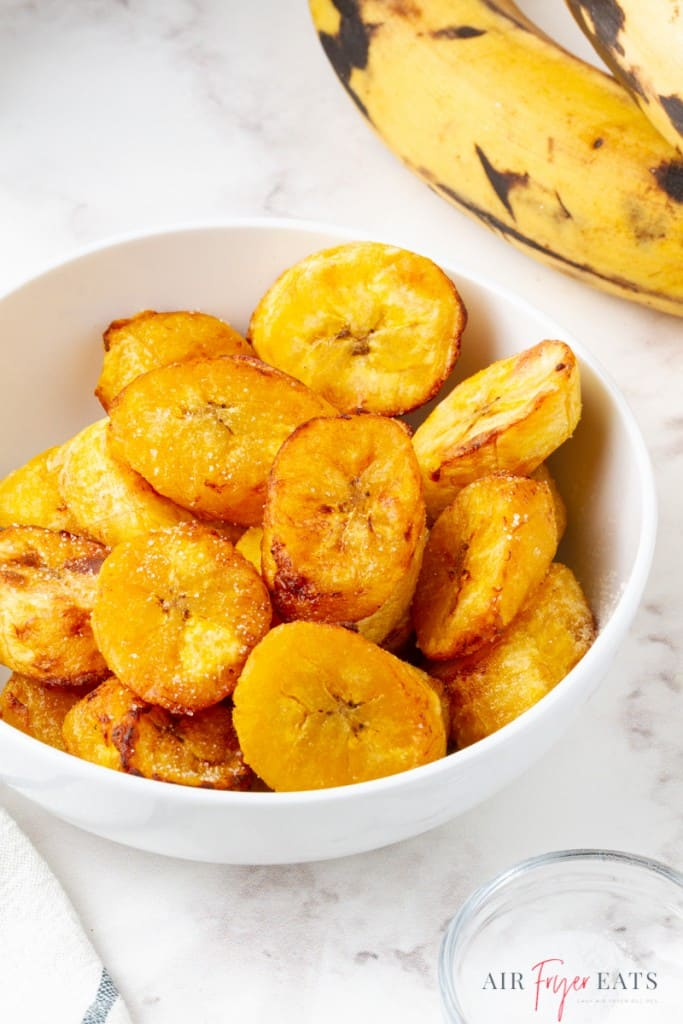 a white bowl filled with cooked plantain slices.