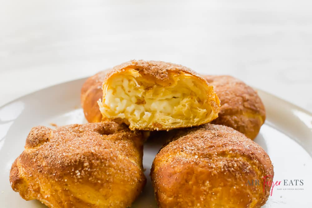 a plate of small rolls topped with pumpkin spice and sugar. One is bitten into and has a cream cheese center.