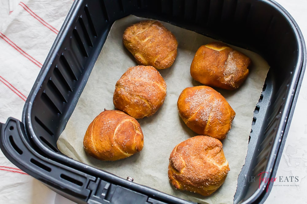 top down view of pumpkin spice bites, which are crescent rolls topped with pumpkin spice, in an air fryer basket lined with parchment