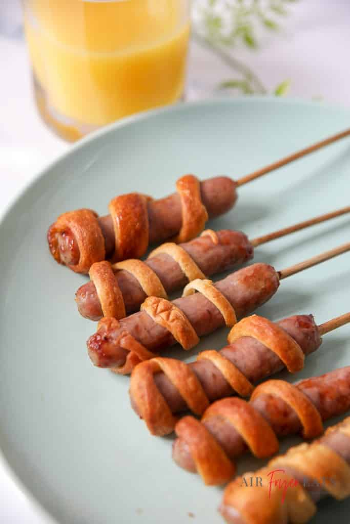 five breakfast sausages, each wrapped in strips of dough and on bamboo skewers, on a light blue/green plate.