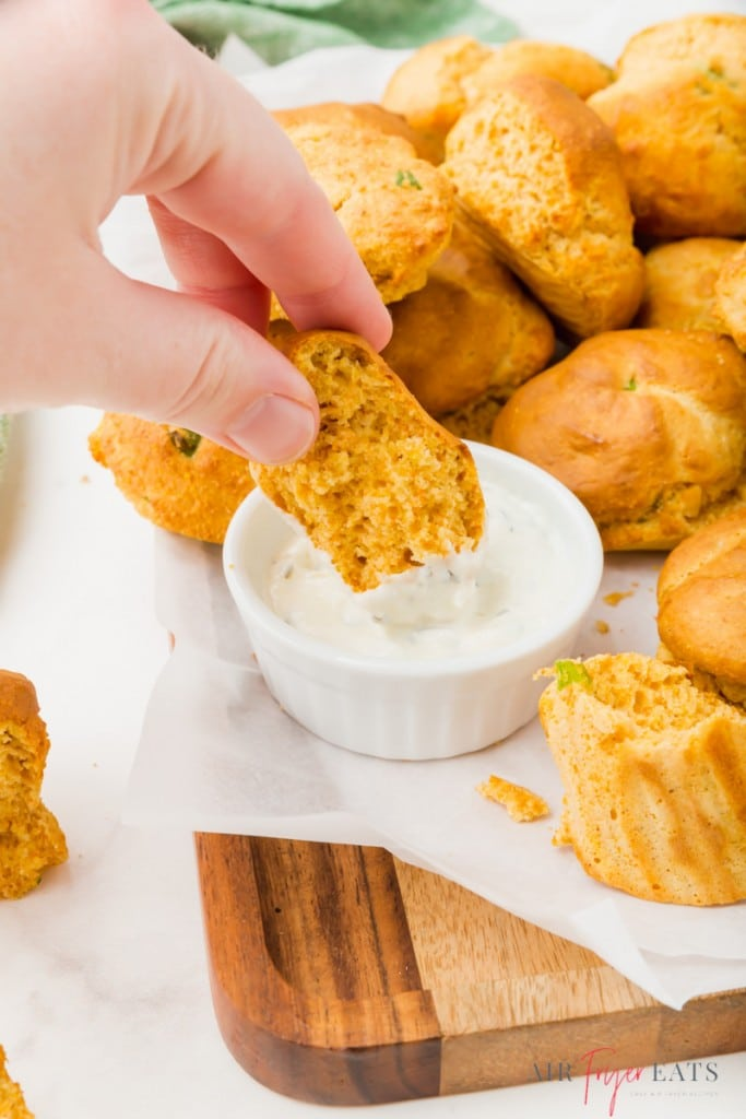 air fryer hushpuppy dipping into a creamy sauce
