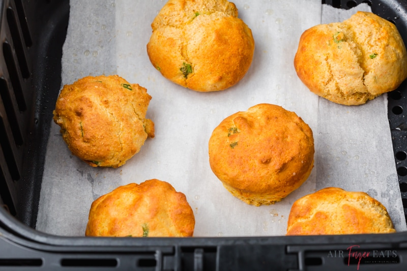 air fryer hush puppies in an air fryer basket lined with parchment paper