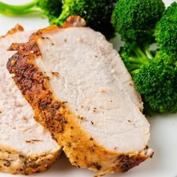 closeup of a sliced pork roast with a side of broccoli