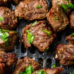 small pieces of steak in an air fryer basket, topped with parlsley