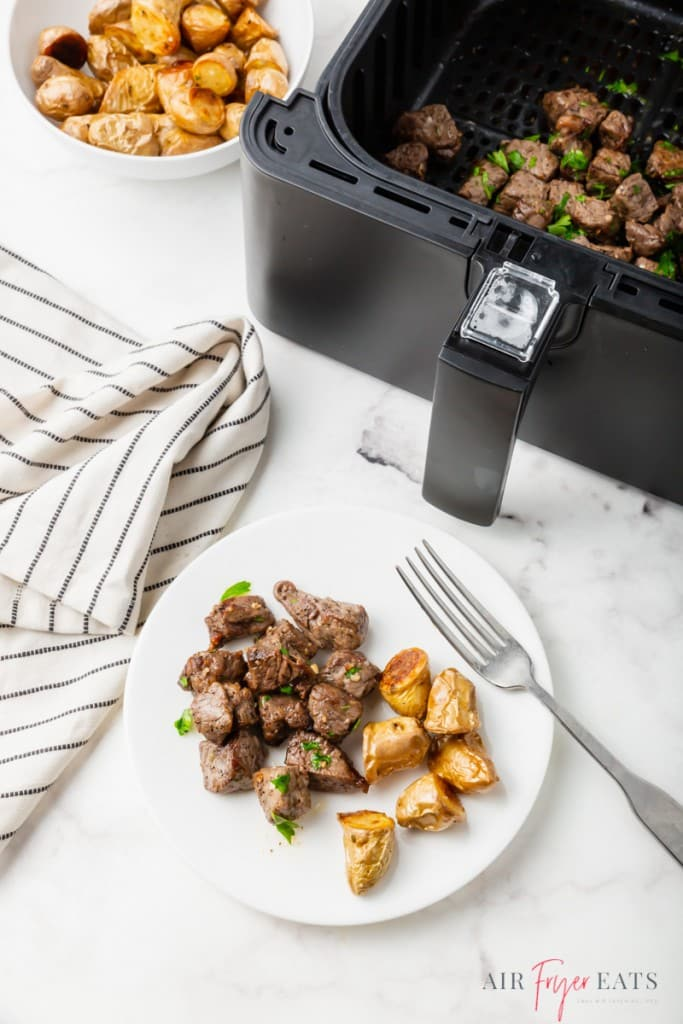 a plate of steak bites and potatoes, next to an air fryer basket