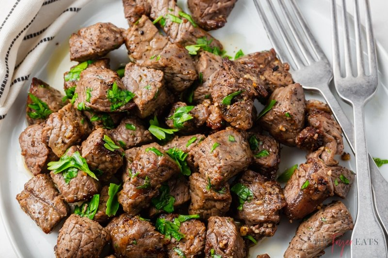 closeup shot of a plate of steak bites topped with parsley,