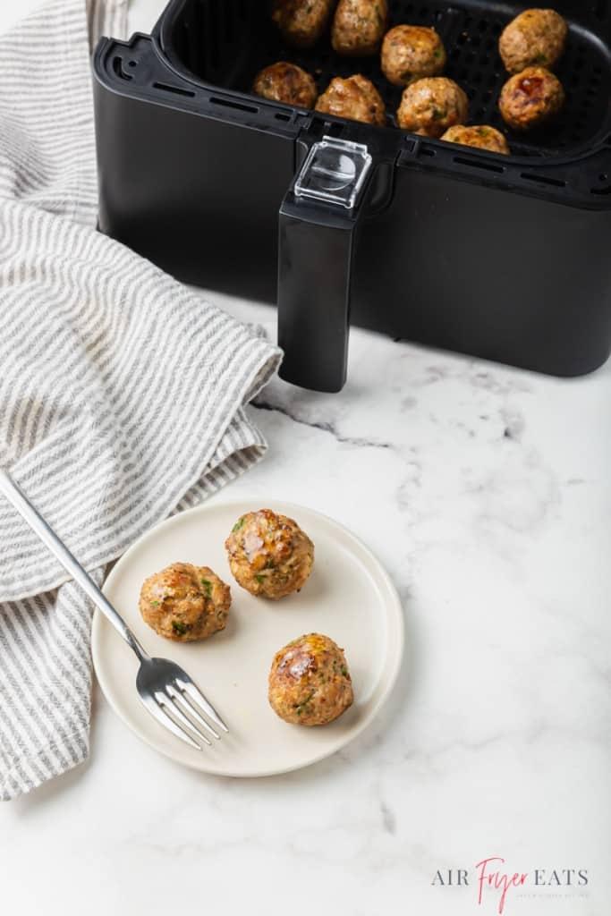 a plate of three meatballs next to an air fryer basket
