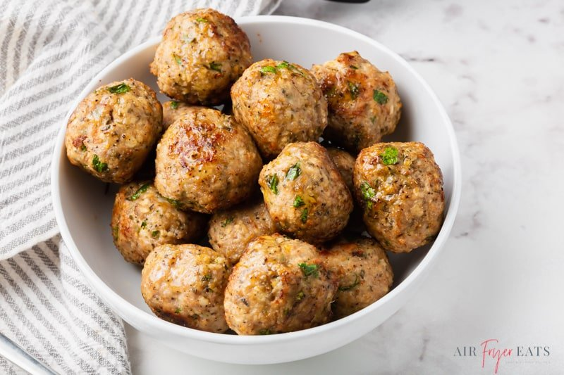 a white bowl filled with cooked turkey meatballs