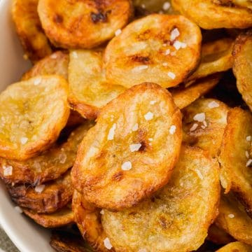 a closeup view of a plate of crispy banana chips with salt.