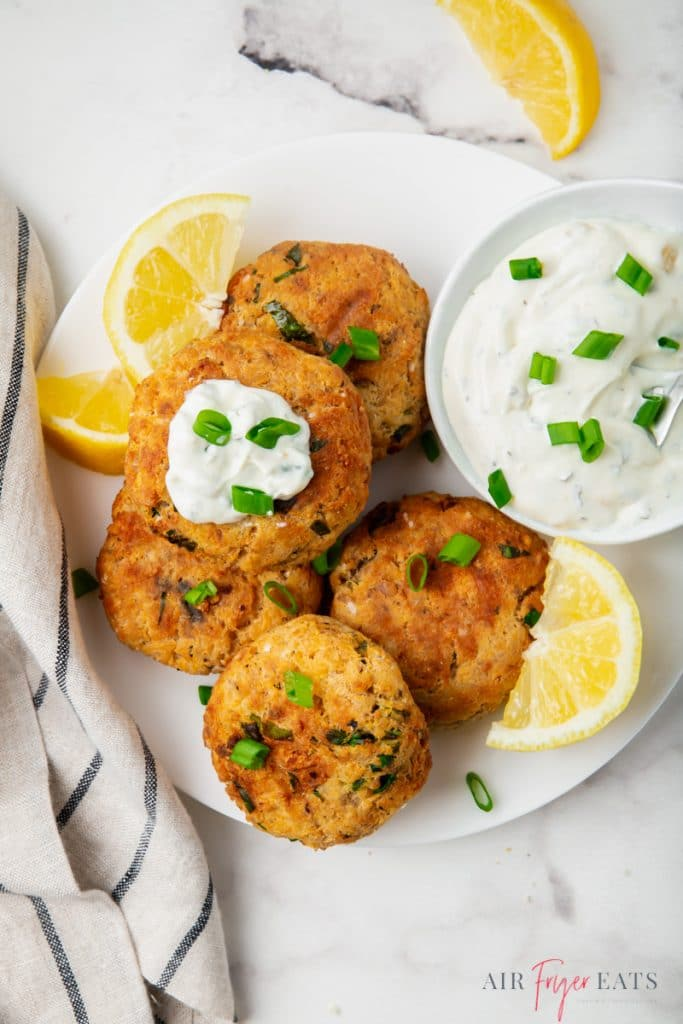 a plate of salmon patties with lemons and tartar sauce
