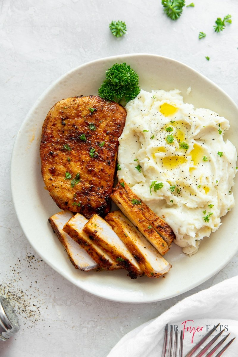 air fryer pork chop with no breading, one whole, another sliced thinly, with a side of mashed potatoes and a parsley sprig