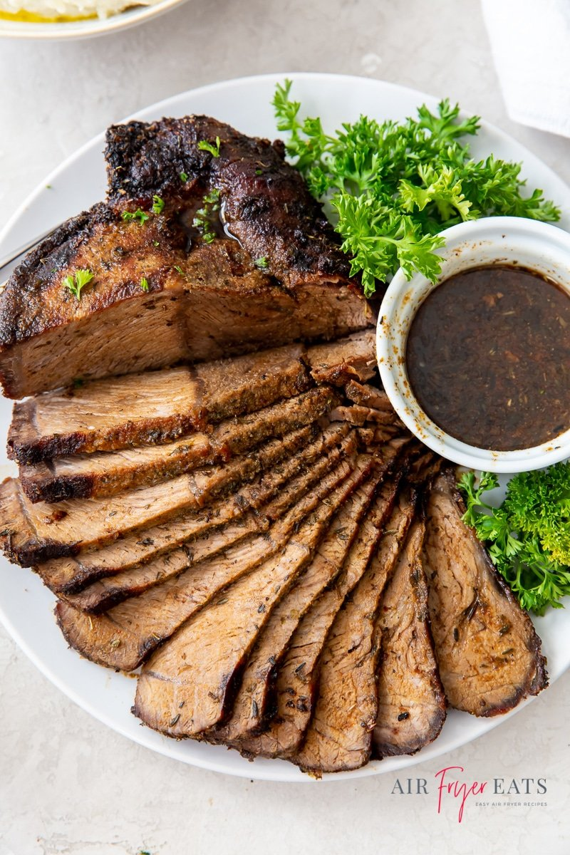 sliced roast beef fanned out on a plate with a cup of au jus and green lettuce garnish