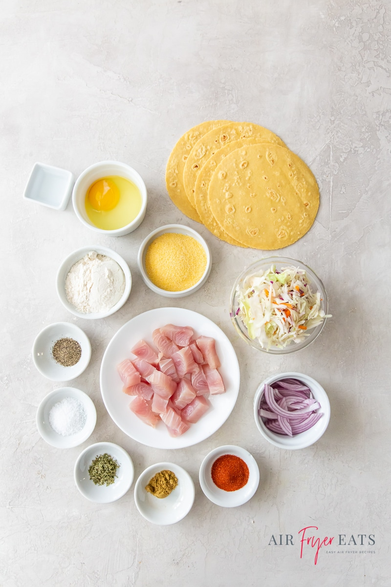 ingredients for fish tacos in the air fryer, all in separate bowls on a marble countertop