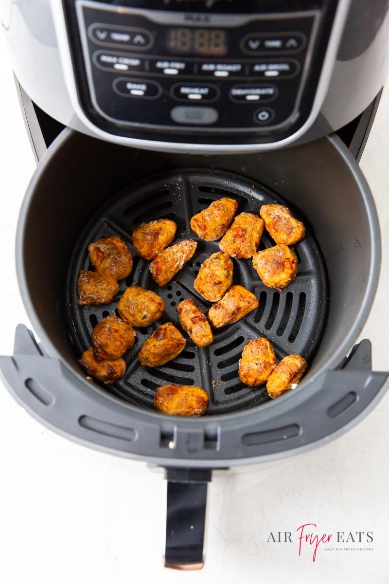 crispy fish pieces in a round, black, air fryer basket.