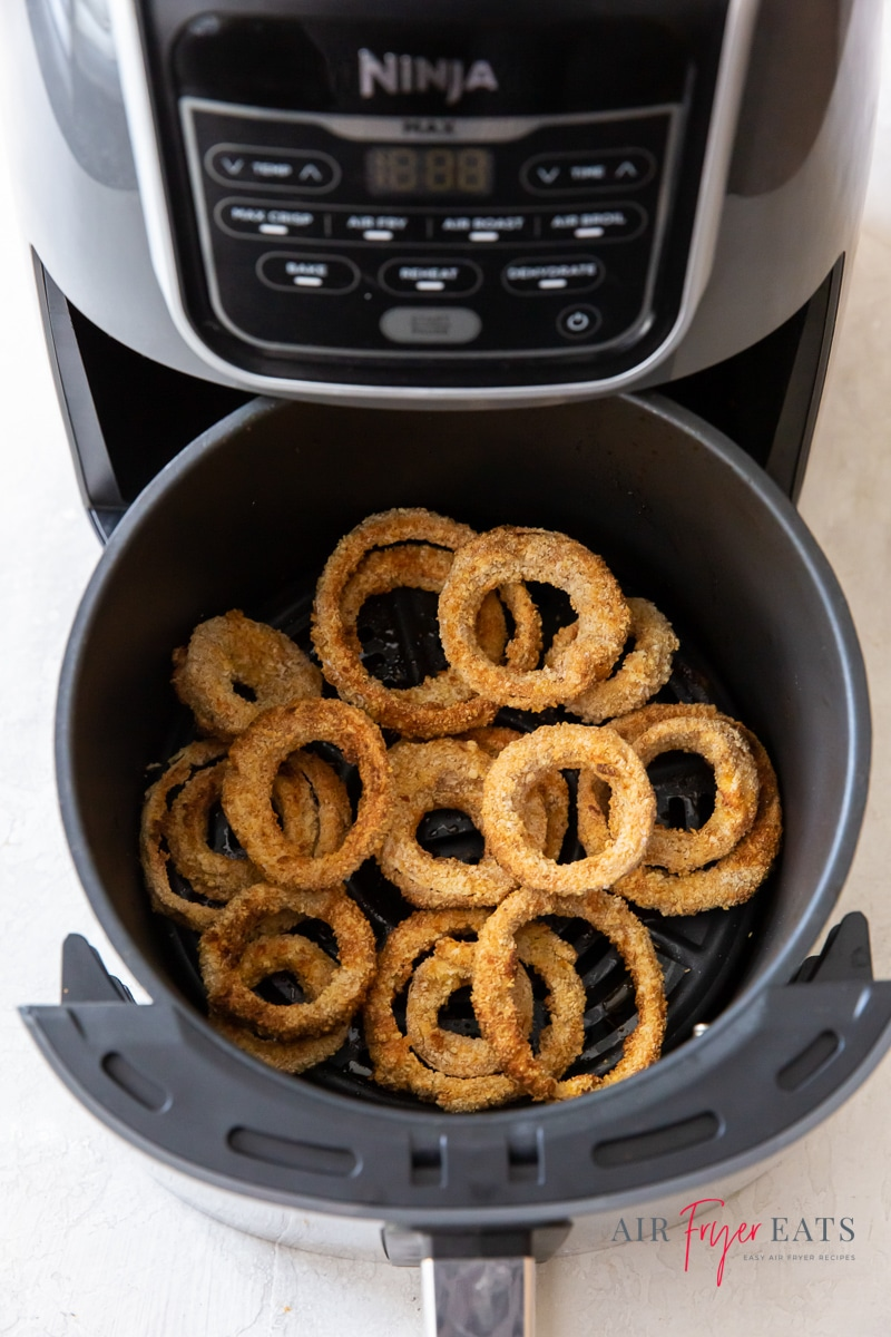 View of cooked onion rings in a round air fryer basket.