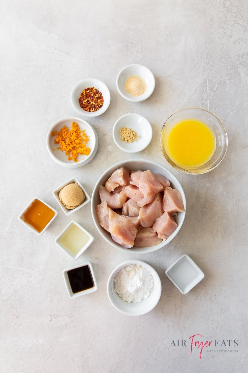 ingredients for air fryer orange chicken, all in separate bowls on a countertop.