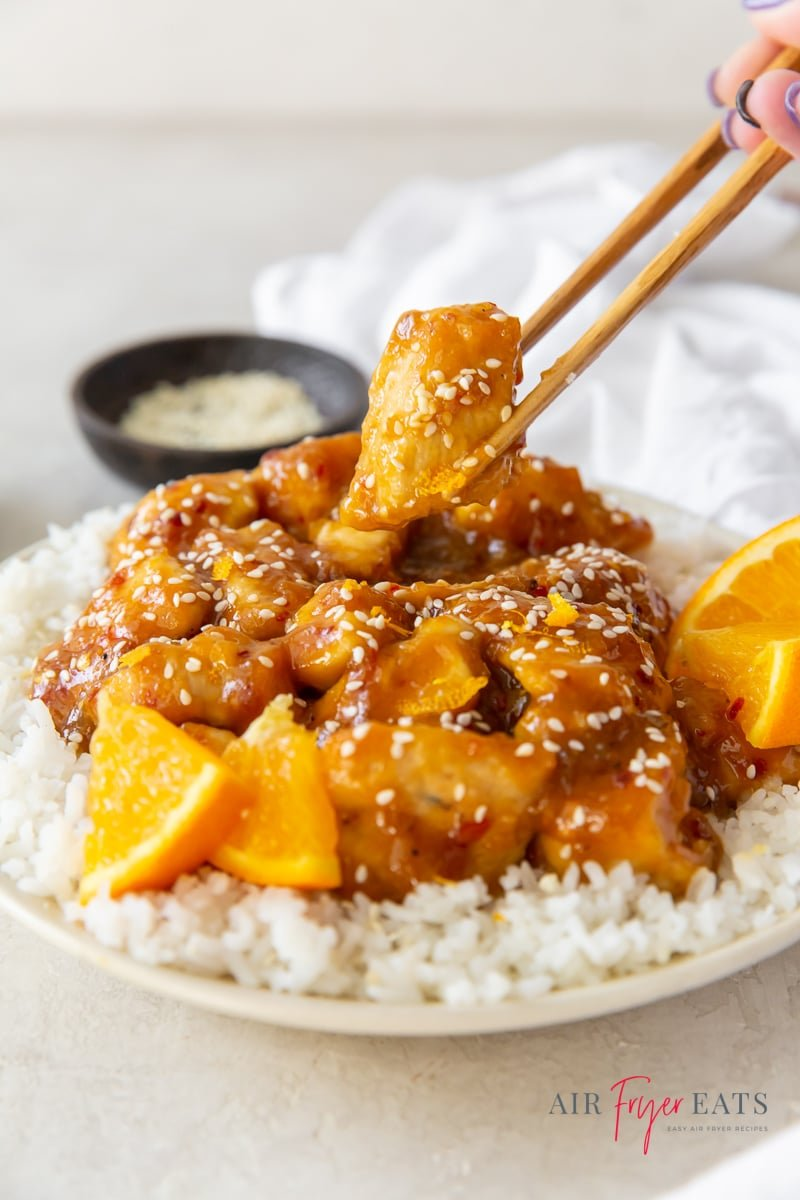 a plate of orange chicken over rice, a pair of chopsticks is grabbing a piece of chicken