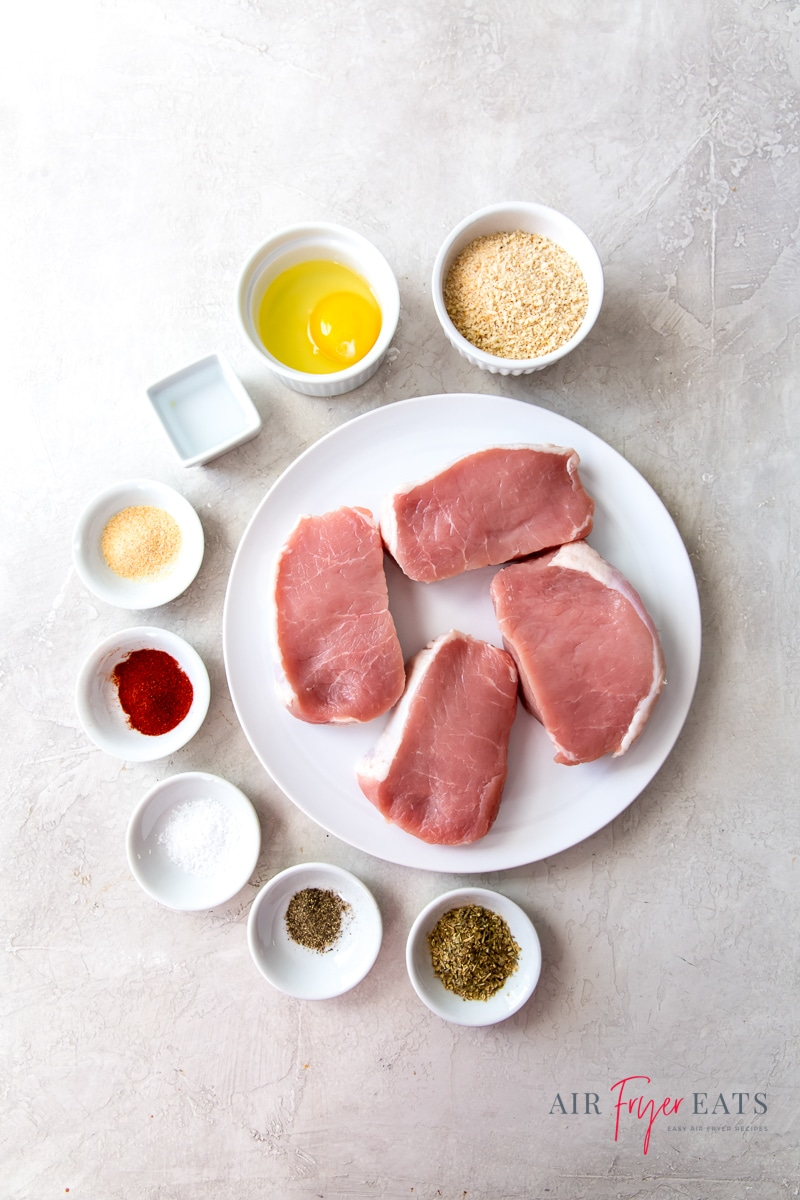 Ingredients for air fryer breaded pork chops, each in separate bowls on a marble counter. A round plate of raw boneless porkchops has 8 small bowls of seasonings and other ingredients surrounding it on the left side.