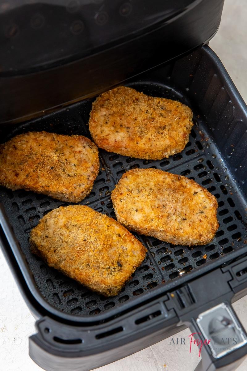 four fried boneless pork chops in a square air fryer basket