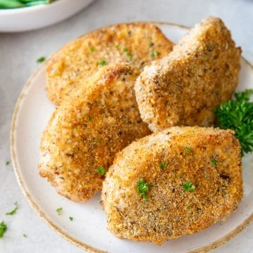 four breaded boneless pork chops on a white plate, garnished with curly parsley