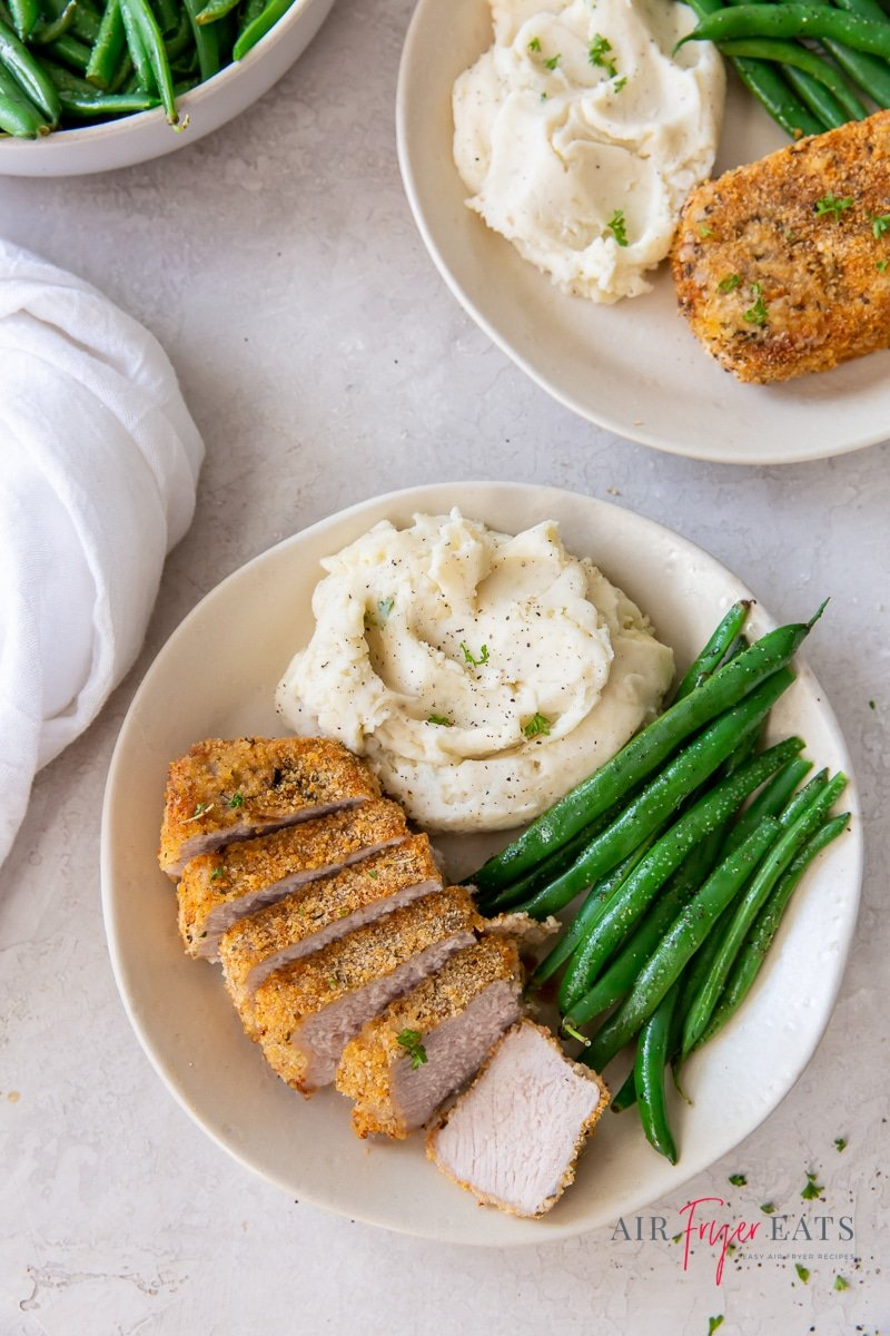 a round white plate with mashed potatoes, whole steamed green beans, and sliced breaded pork chop