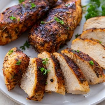 Three chicken breasts that were cooked in air fryer, on a white plate. One is sliced neatly.
